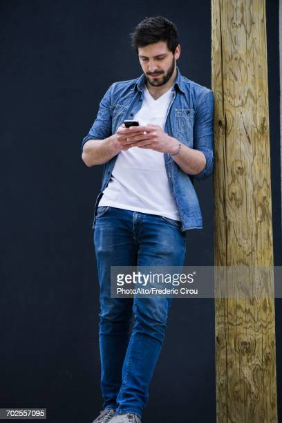 Young man text messaging on cell phone