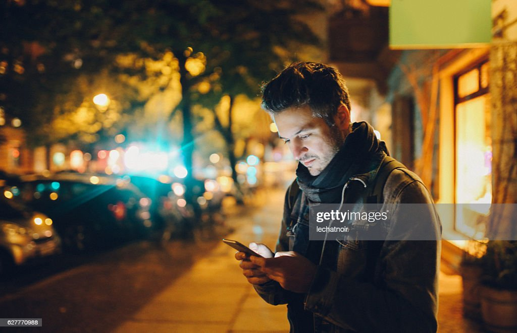 Young man texting in Berlin : Stock Photo