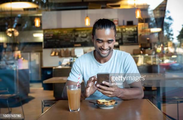 junger mann sms auf seinem handy in einem café - minderheit stock-fotos und bilder