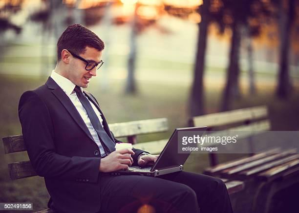 Jeune homme à envoyer des SMS sur un ordinateur portable