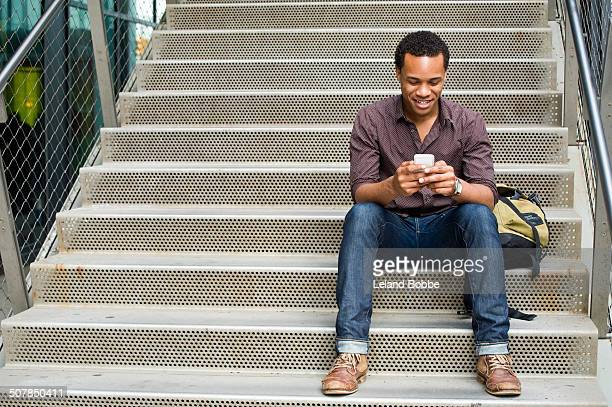 young man texting on smartphone on city stairway - black jeans foto e immagini stock