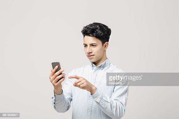 young man texting on smartphone - all shirts ストックフォトと画像