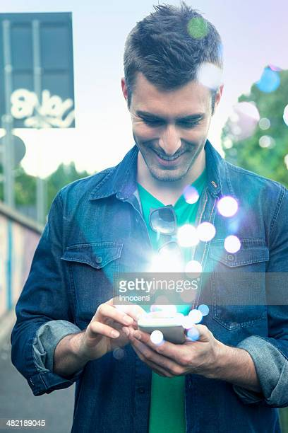 Young man texting on smartphone with glowing lights coming out of it