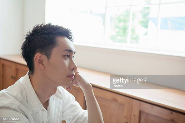 Young man thinking in room