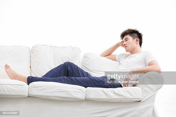 Young man thinking on couch