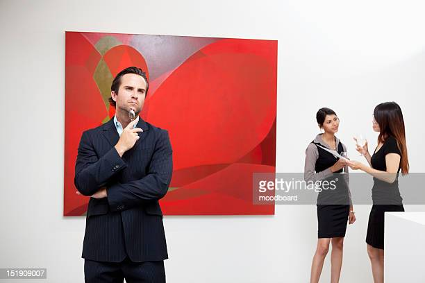 Young man thinking with two women talking in background in art gallery