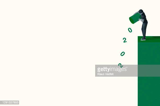 young man throwing 2020 from green garbage bin - oresund region stock pictures, royalty-free photos & images