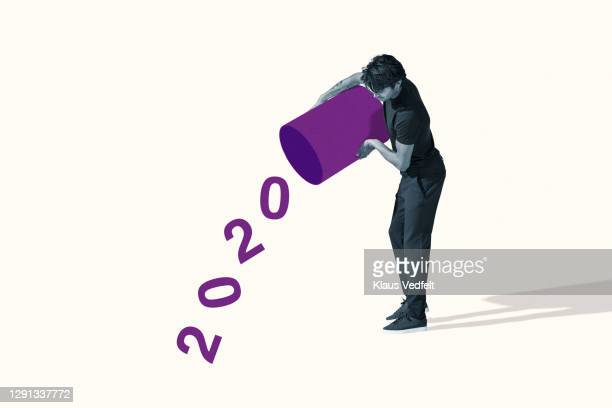 young man throwing 2020 from purple garbage bin - the end stock pictures, royalty-free photos & images