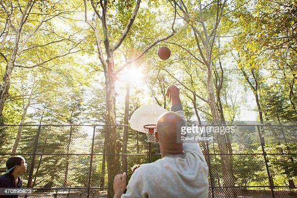 Young man throwing basketball towards goal