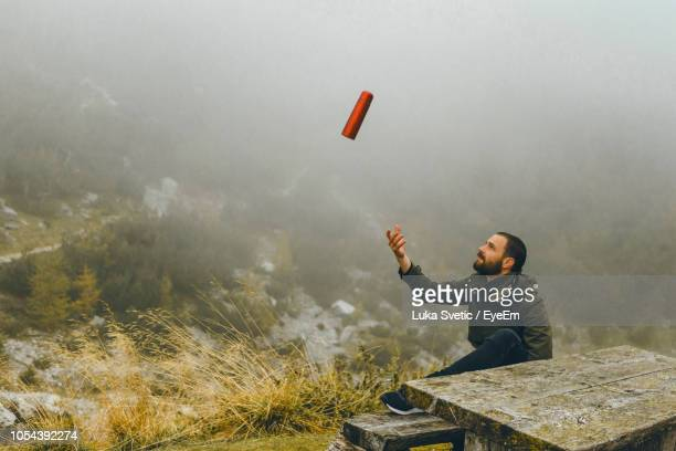 Young Man Throwing Bottle While Sitting At Table Against Landscape