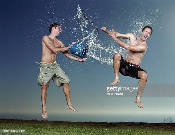 Young man throwing bucket of water at friend