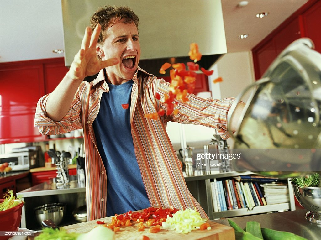 Young man throwing red bell peppers into strainer : Foto de stock