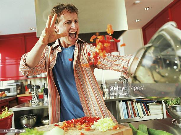 Young man throwing red bell peppers into strainer