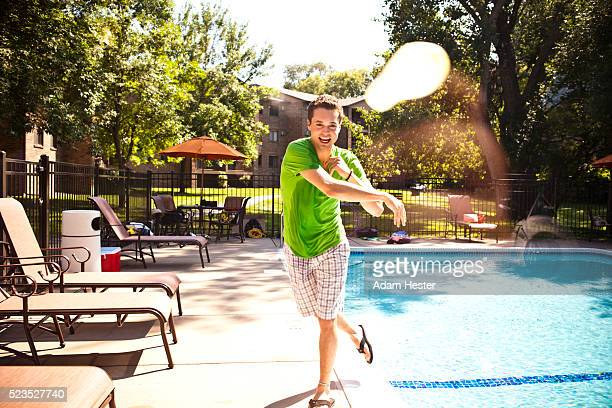 Young man throwing small balloon filled with water at camera