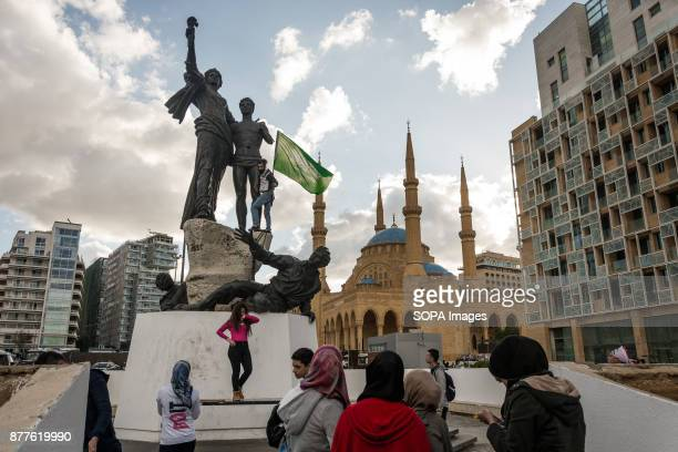 A young man throws down a Saudi flag hoisted atop Beirut's bulletridden Martyr statue 'This is Lebanon' shouted his friend Lebanon marked its 74th...