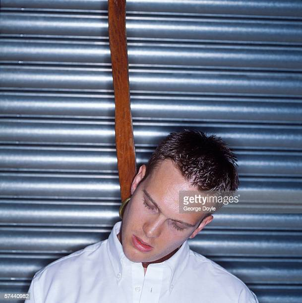 young man tied from his neck against a shutter of a shop - death photos stock photos and pictures