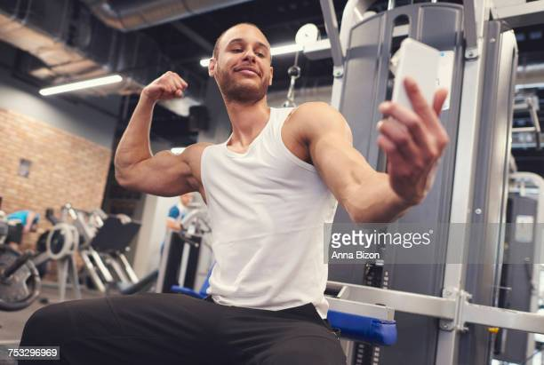 Young man tightening muscles over taking selfie. Mielec, Poland