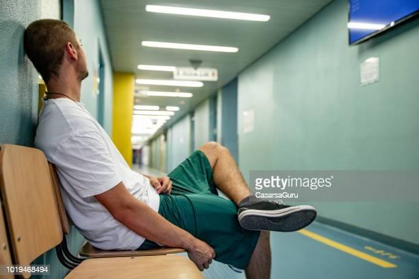junger mann müde des wartens im krankenhaus wartezimmer - film and television screening stock-fotos und bilder