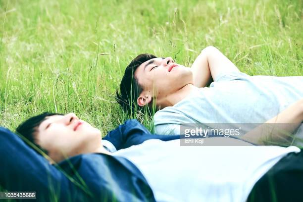 a young man to relax in the green grass - 心の平穏 ストックフォトと画像