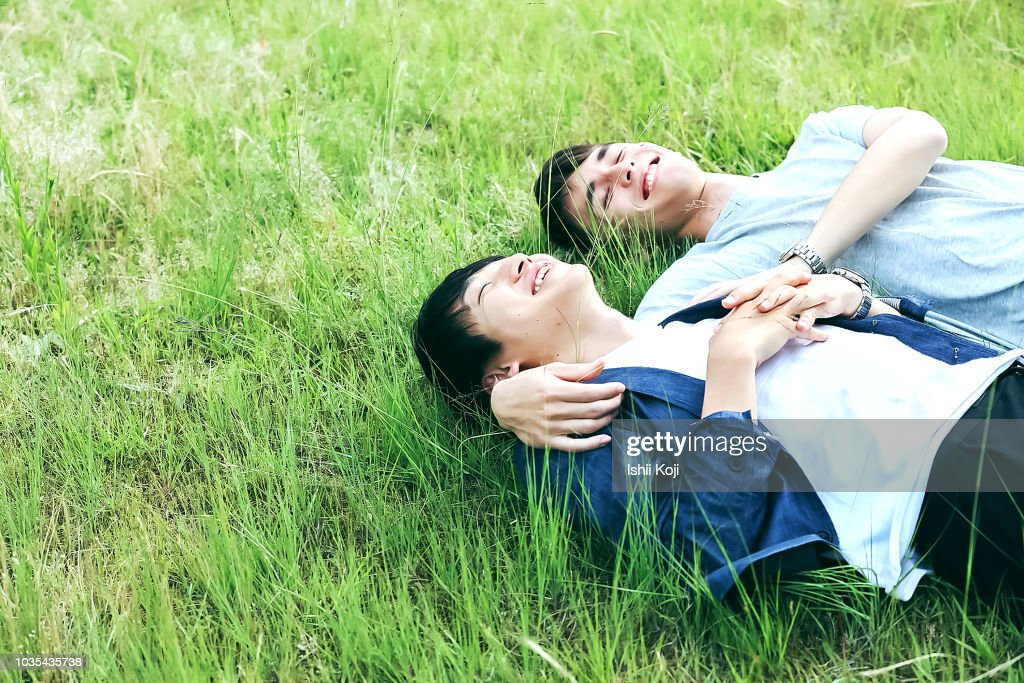 A young man to relax in the green grass : Stock Photo