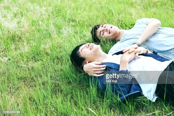 a young man to relax in the green grass -  lgbtqi ストックフォトと画像