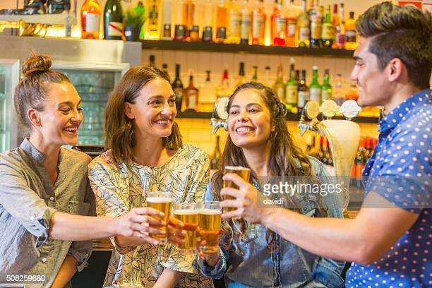 Young Man Toasting With Drinks and Girls in a Bar