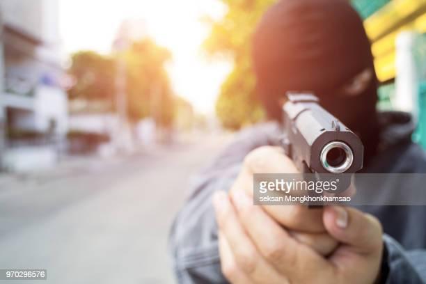 young man took aim with pistol near village roads. - kopfschuss stock-fotos und bilder