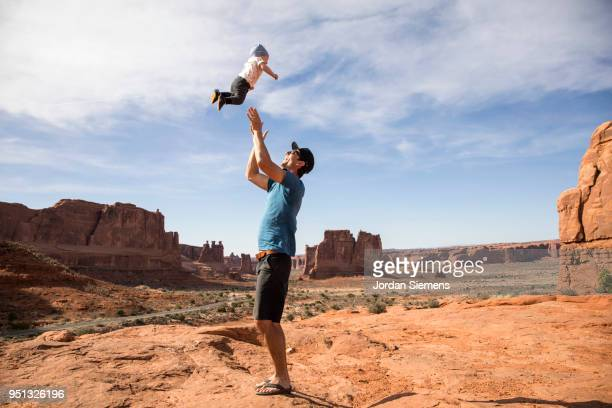 A young man tossing his baby boy in the air.