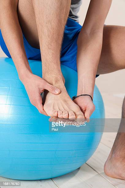 young man touching his injured foot