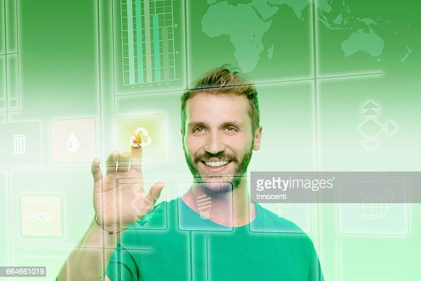 Young man touching recycling icon on graphical screen