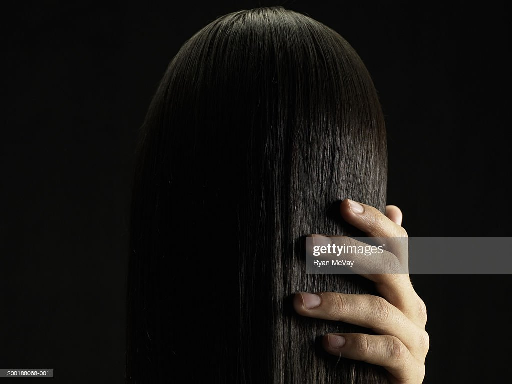 Young man touching young woman's hair, rear view, close-up : Stock Photo