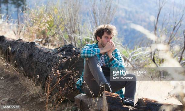 Young man, tourist, hiker and hipster, resting and playing the mouth organ in mountain in Yosemite National Park