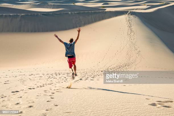 Young man, tourist running down sand dune, Mesquite Flat Sand Dunes, Death Valley, Death Valley National Park, California, USA