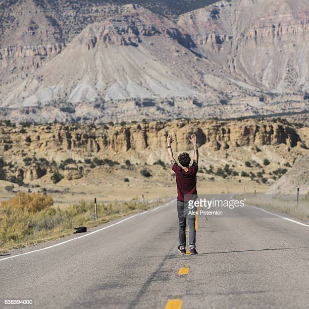 Young man, tourist, walking on the highway in Utah, USA