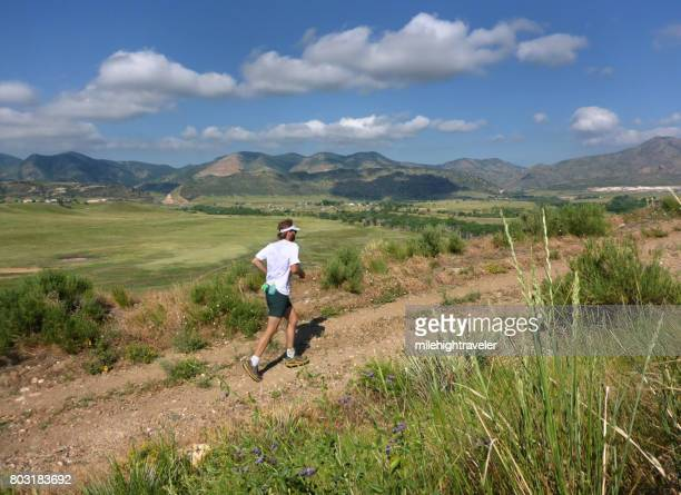 young man trail running bear creek lake park front range rocky mountains colorado - front range mountain range stock pictures, royalty-free photos & images