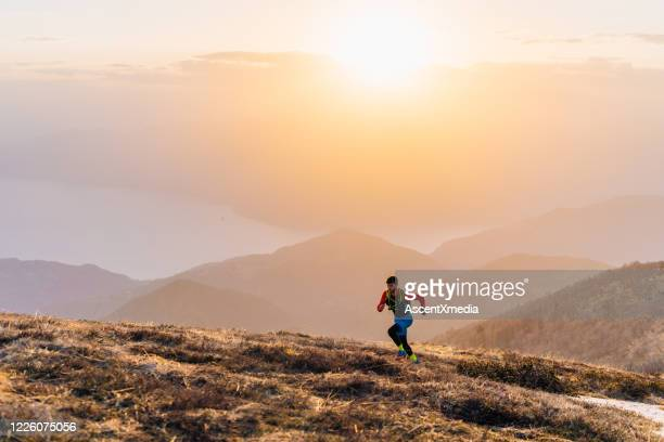 young man trail runs up mountain at sunrise - forward athlete stock pictures, royalty-free photos & images