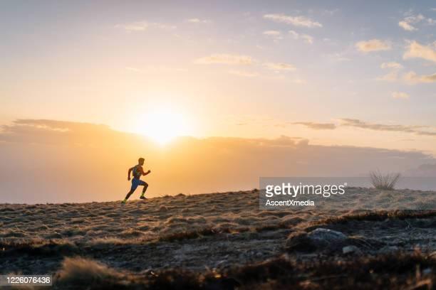 trilha de jovem corre montanha ao nascer do sol - escapismo - fotografias e filmes do acervo