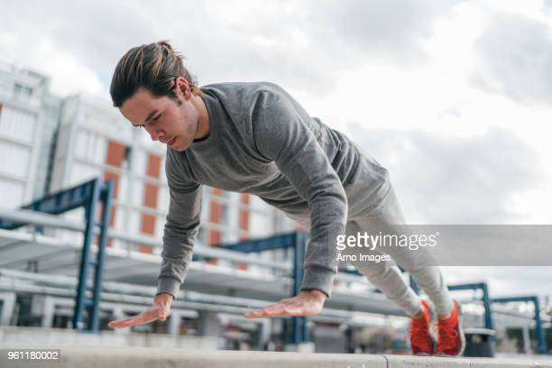 young man training, doing push up in city, low angle view - forza italia foto e immagini stock