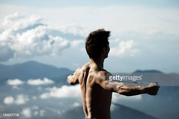 young man training in the mountain,rubber band