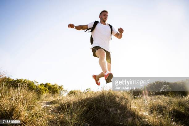 Young man training, jumping mid air from sand dunes