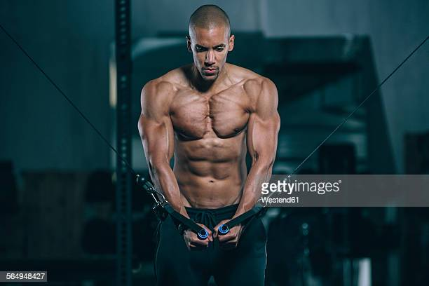 Young man training pectoral muscles at cable crossover in gym