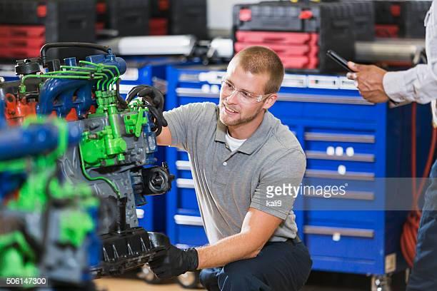 Junger Mann training auf ein auto mechanic