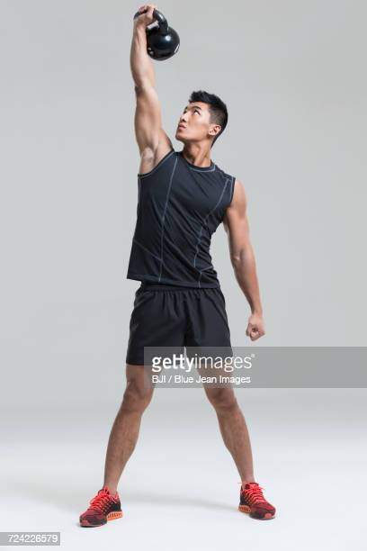young man training with kettlebell - benen gespreid stockfoto's en -beelden