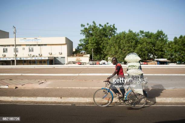 A young man transports several bags on a bicycle Street scene Bamako on April 07 2017 in Bamako Mali