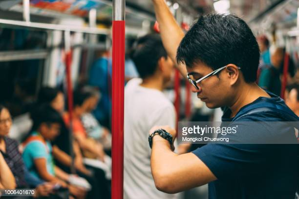 young man traveler is visiting at hongkong by subway mtr train and looking watch. the mass transit railway is the rapid transit railway system in hong kong. - crowded subway stock photos and pictures