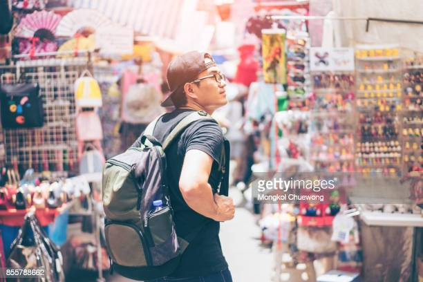 young man traveler is visiting at mongkok in hong kong. - toerist stockfoto's en -beelden