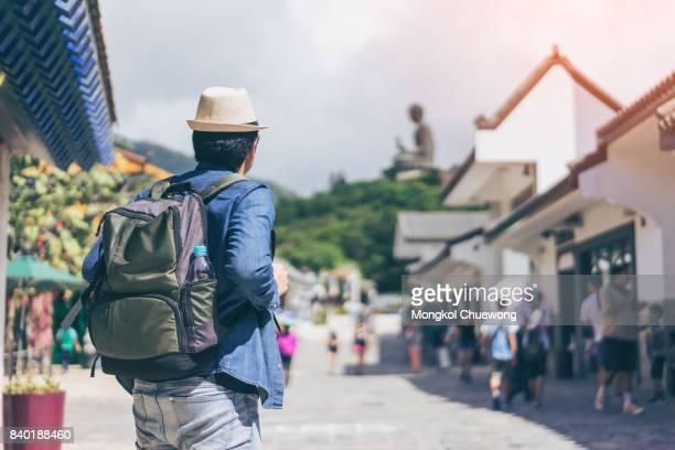 Young man traveler is visiting at The enormous Tian Tan Buddha at Po Lin Monastery in Hong Kong