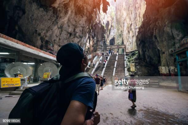 Young man traveler with backpack traveling into Batu Caves Lord Murugan Statue and entrance at Hindu Temple near Kuala lumpur Malaysia
