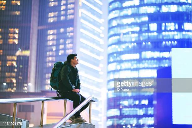 young man traveling alone in the city - nomadic people stock pictures, royalty-free photos & images