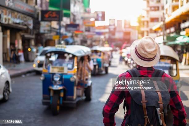 young man traveling backpacker in khaosan road outdoor market in bangkok, thailand - bangkok fotografías e imágenes de stock